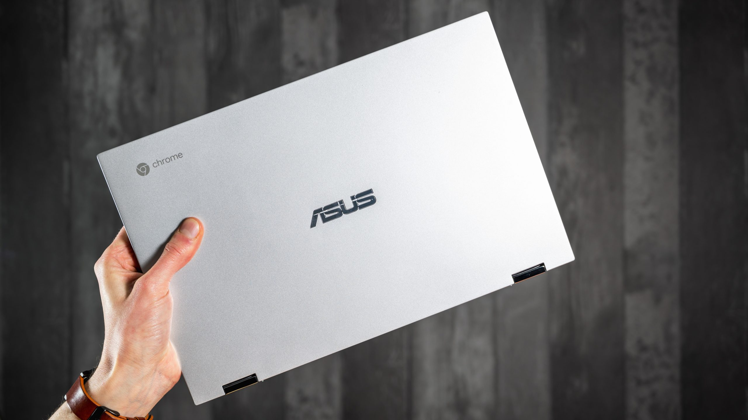 De achterzijde van een Chromebook van ASUS, welke dichtgeklapt wordt opgehouden.