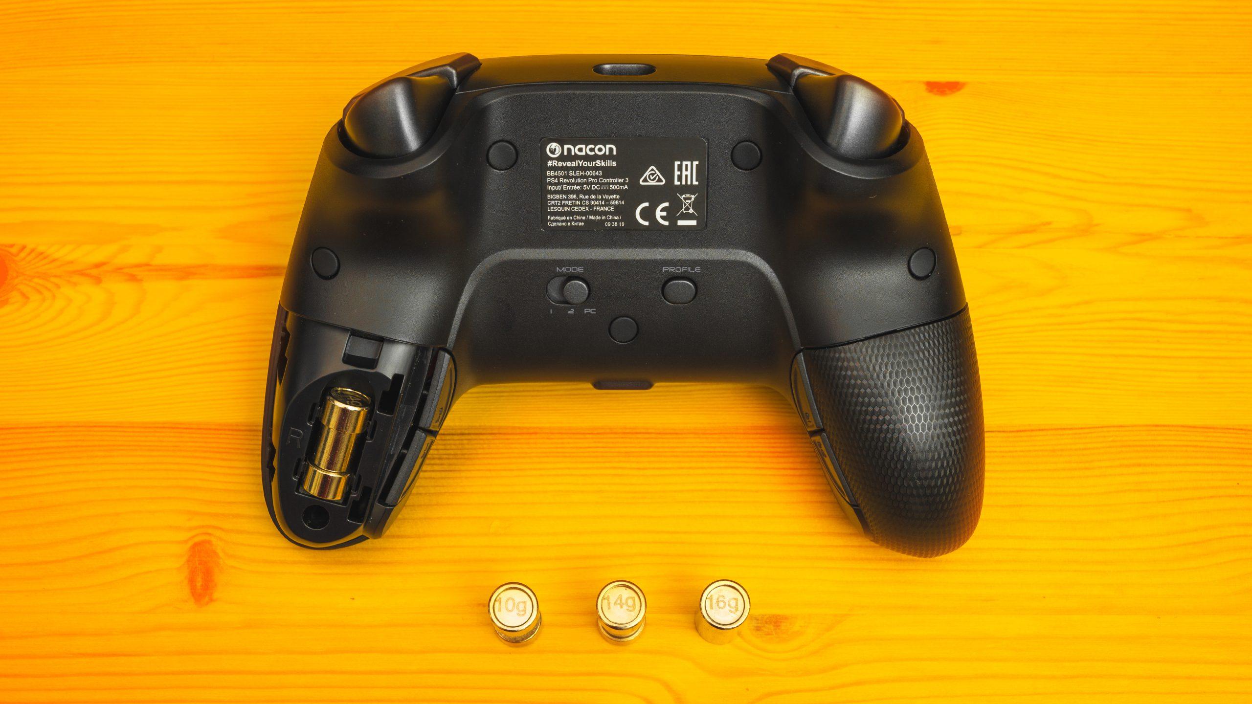Achterzijde van de Nacon Revolution Pro 3 (met daarop verschillende profielknoppen) en drie verschillende gewichtjes, welke in de palmsteunen van de controller geplaatst kunnen worden.