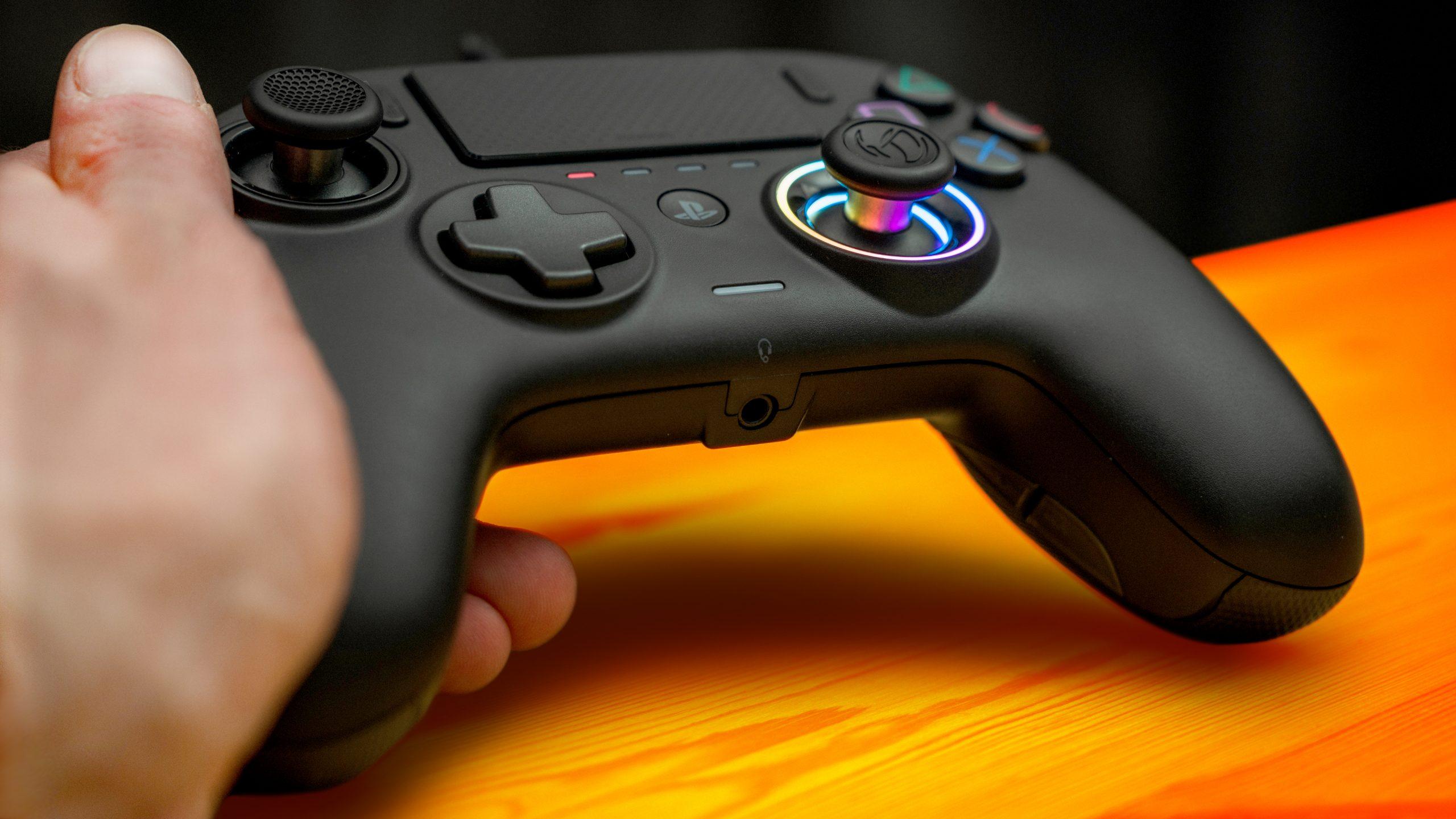 Foto van de Revolution Pro 3-controller van Nacon, welke met de linkerhand vastgehouden wordt. Onderop is de 3.5mm headset-poort te zien.