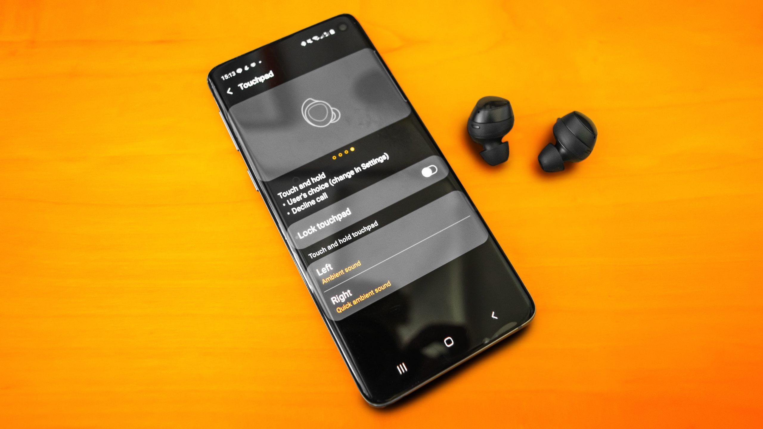 Foto van een smartphone met daarop de Samsung Wearable app, bijgestaan door compatibele draadloze oortjes.