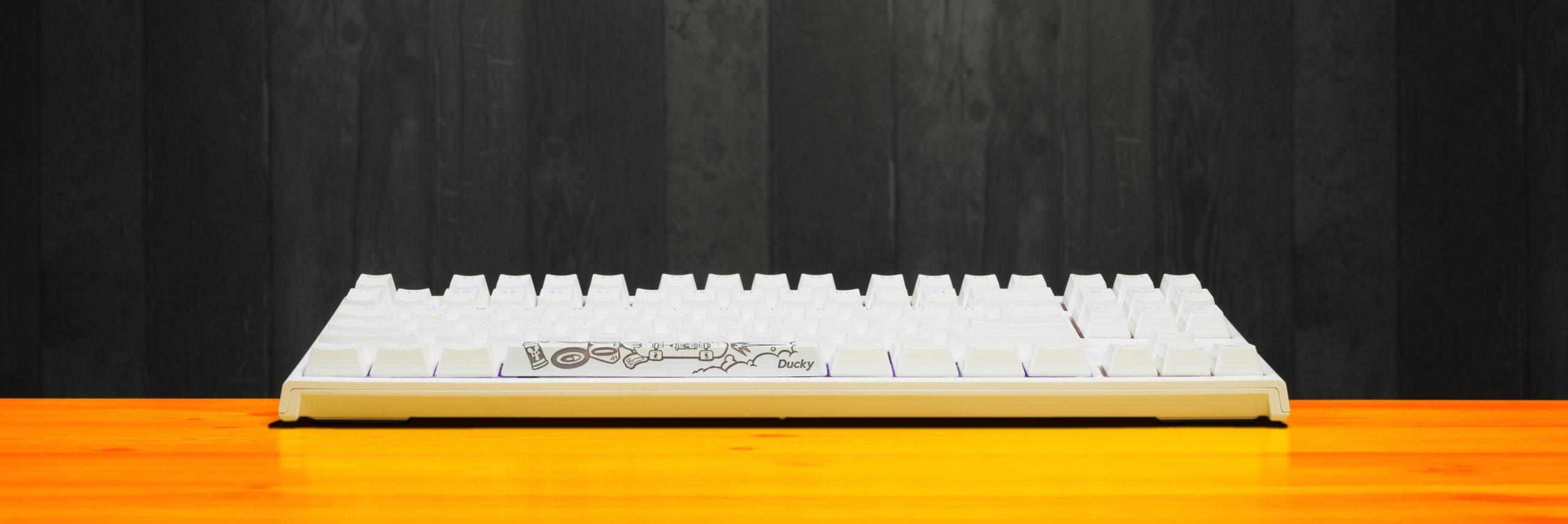 Profielaanzicht van een opstaande Ducky One 2 RGB TKL, met daarop de spatiebalk vervangen met een van de meegeleverde unieke keycaps.