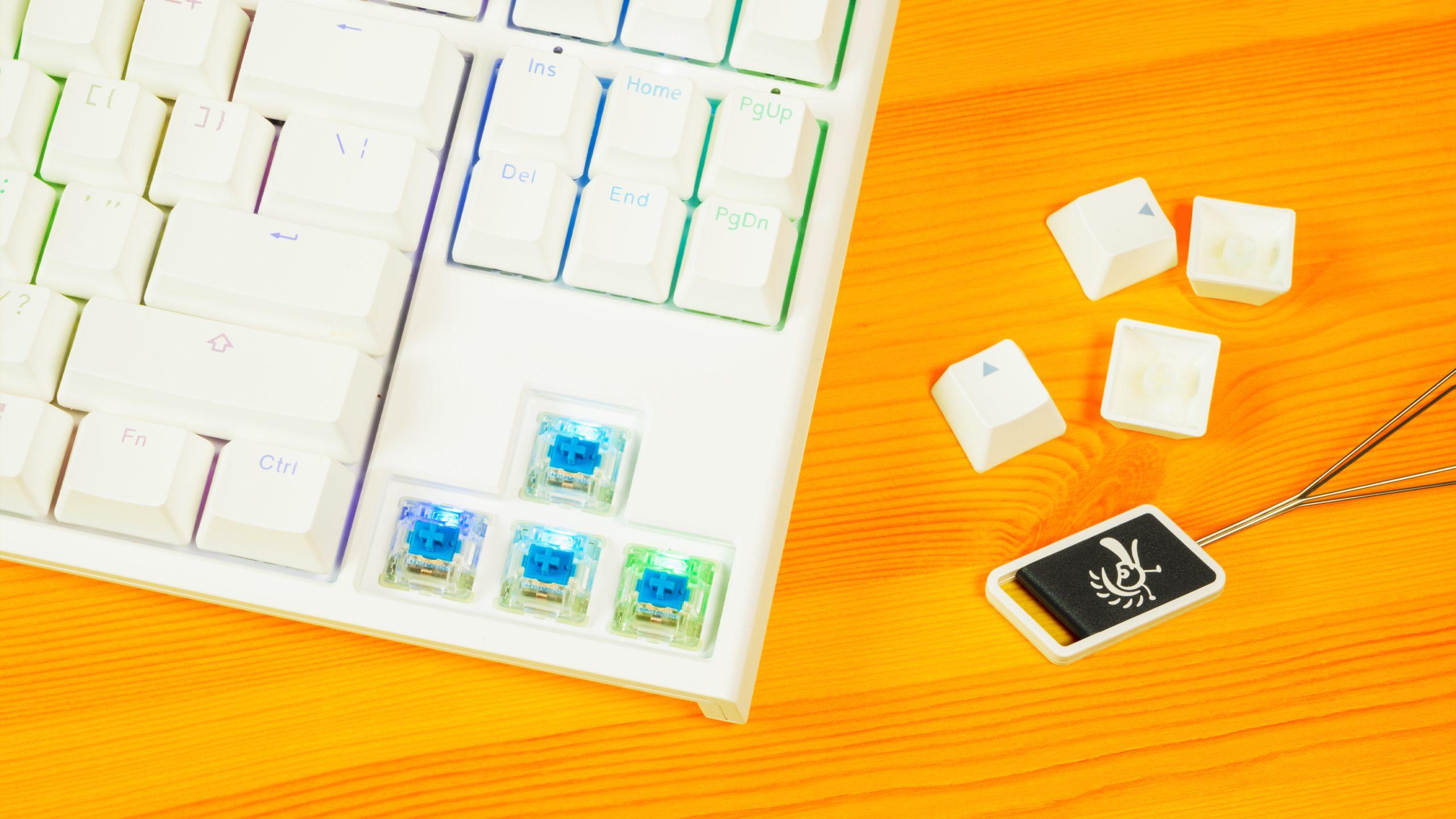 Bovenaanzicht van Cherry MX Blue-schakelaars, een keycap puller van Ducky en legio double-shot, PBT-keycaps.