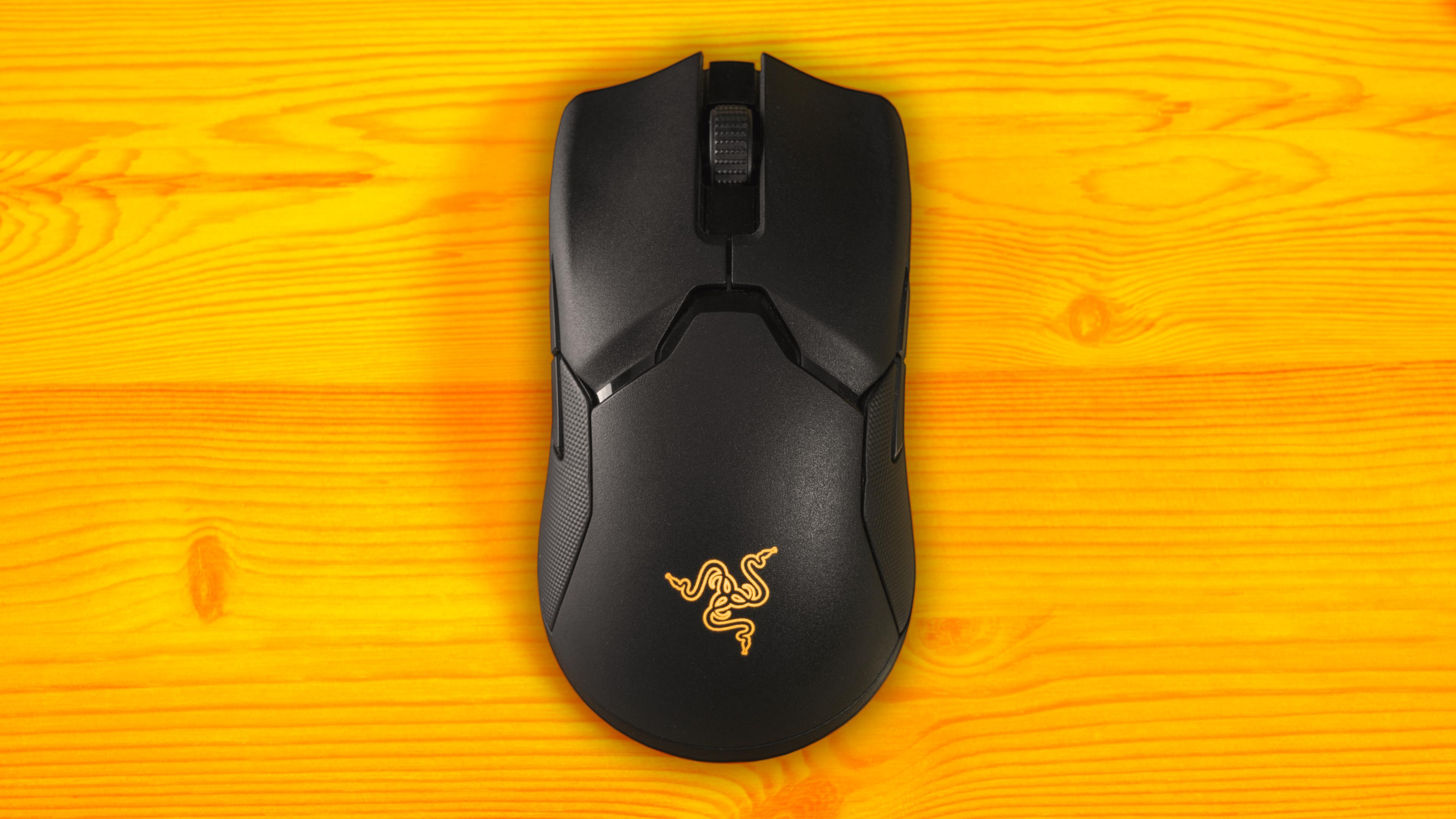 Bovenaanzicht van de Razer Viper Ultimate in gebruik, waarbij het logo oranje verlicht is.
