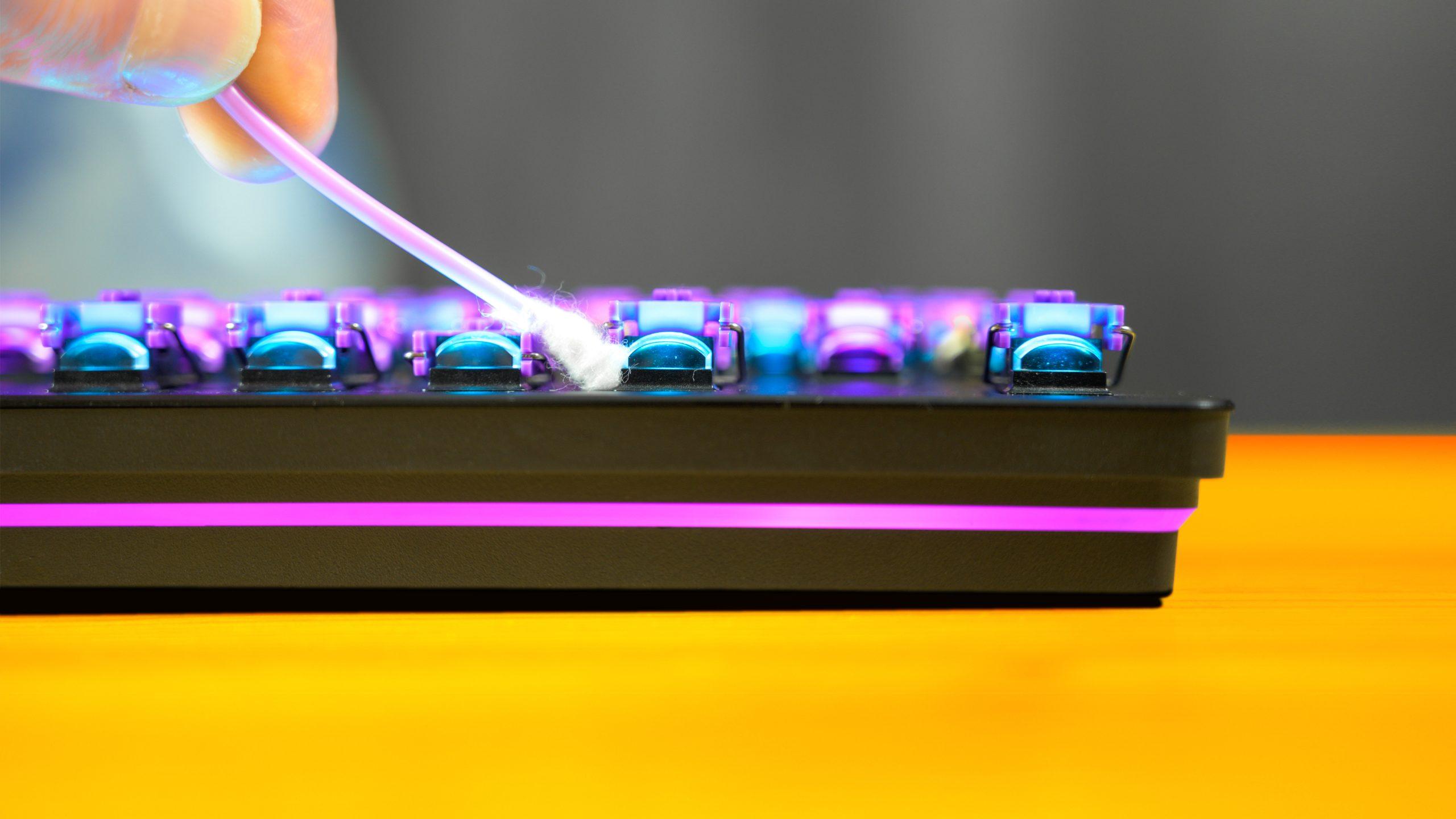 Een mechanisch toetsenbord wordt schoongemaakt met behulp van een wattenstaafje.