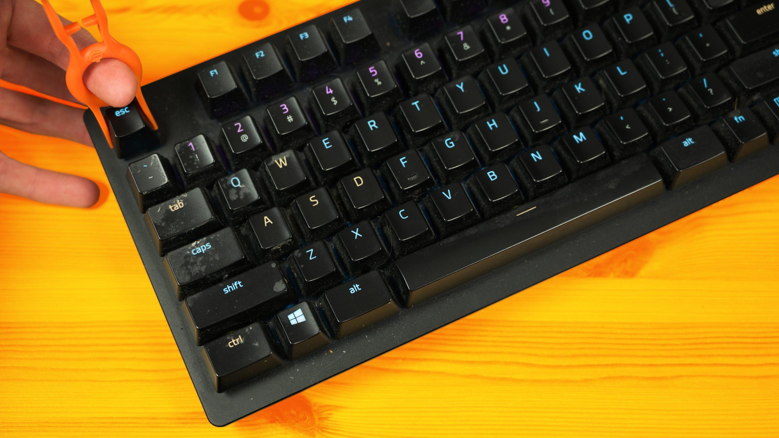 Een aardig vies geworden Razer Huntsman Elite-toetsenbord, waarvan de Escape-knop met een 'keycap puller' verwijderd wordt.