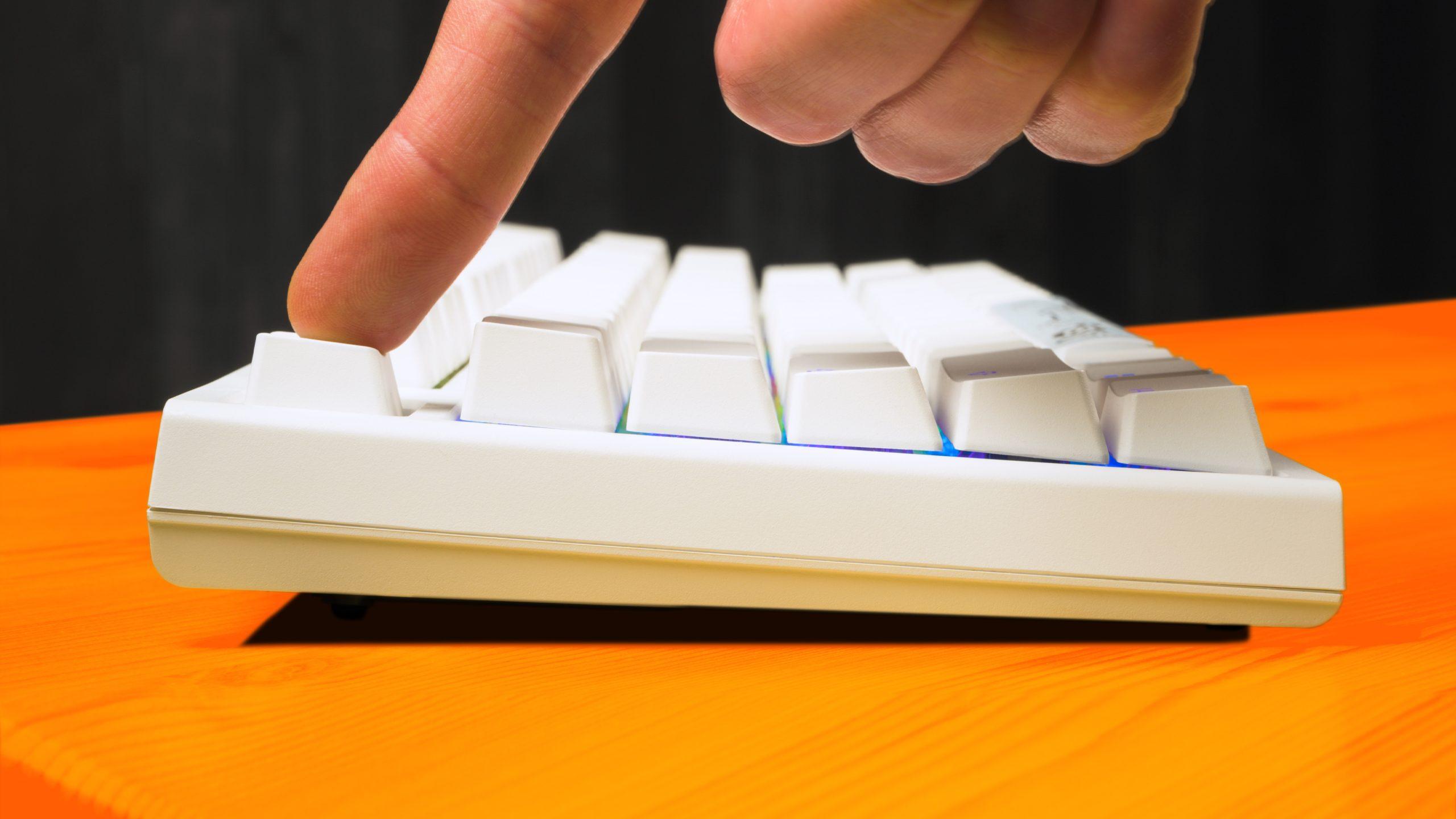 Zij-aanzicht van de Ducky One 2 RGB TKL in het wit, met de voet halverwege uitgeklapt en de regenboogverlichting zichtbaar tussen de keycaps.
