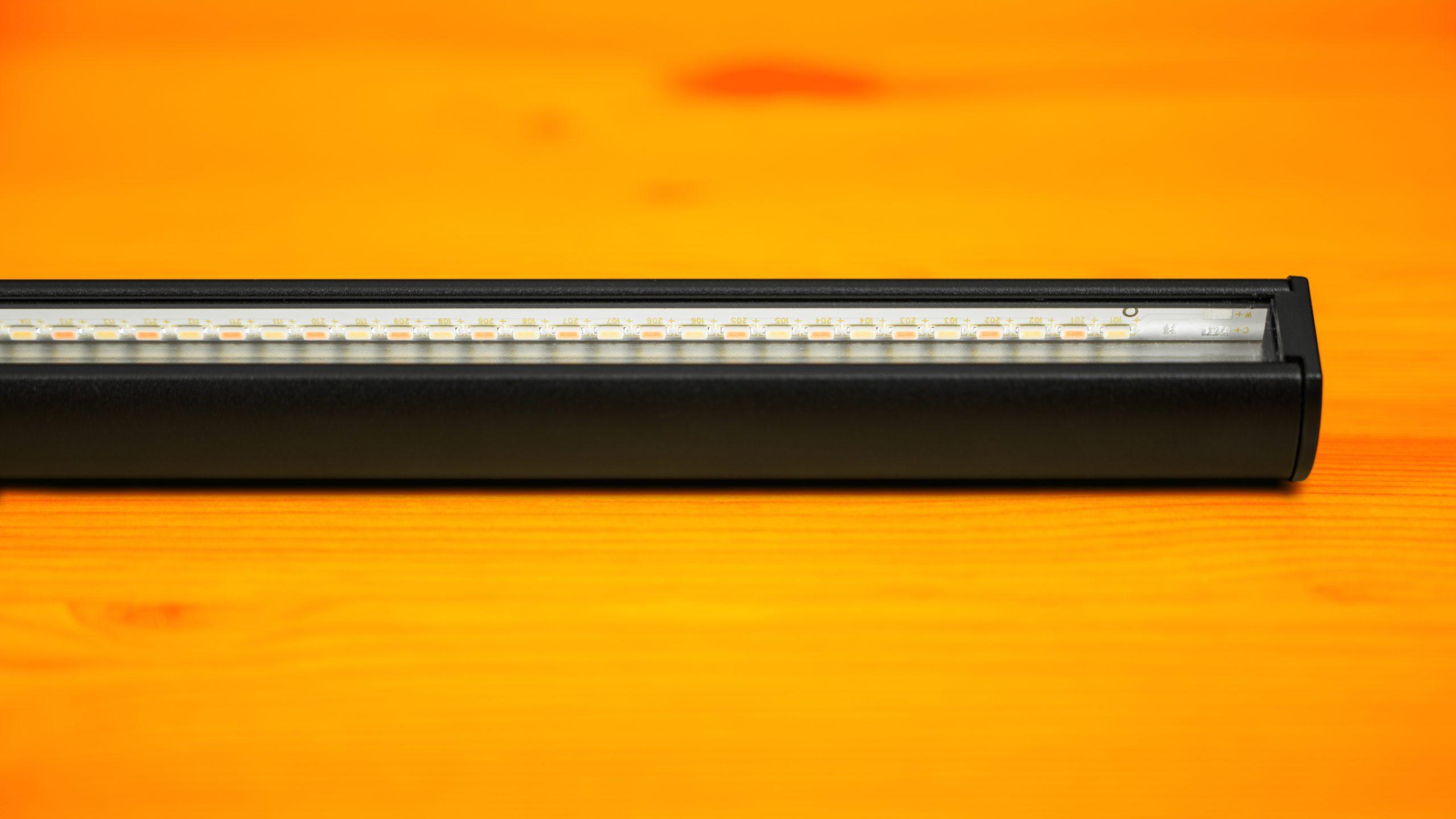 Close-up van de onderzijde van de BenQ ScreenBar, met daarop de LED-verlichting duidelijk zichtbaar.