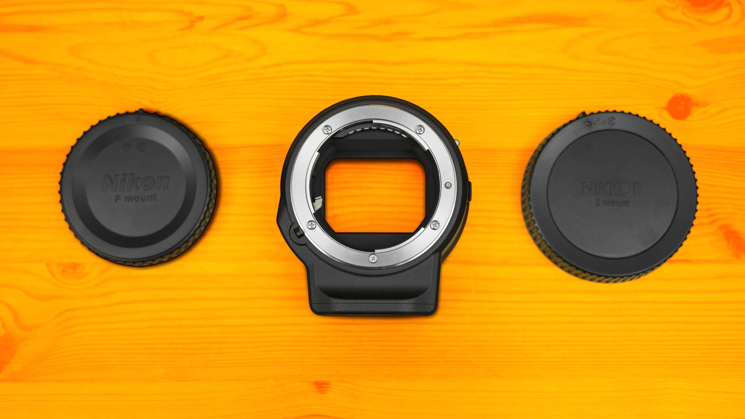 Vooraanzicht van de Nikon FTZ Adapter, met aan weerzijdes de doppen voor respectievelijk de F-vatting en Z-vatting.
