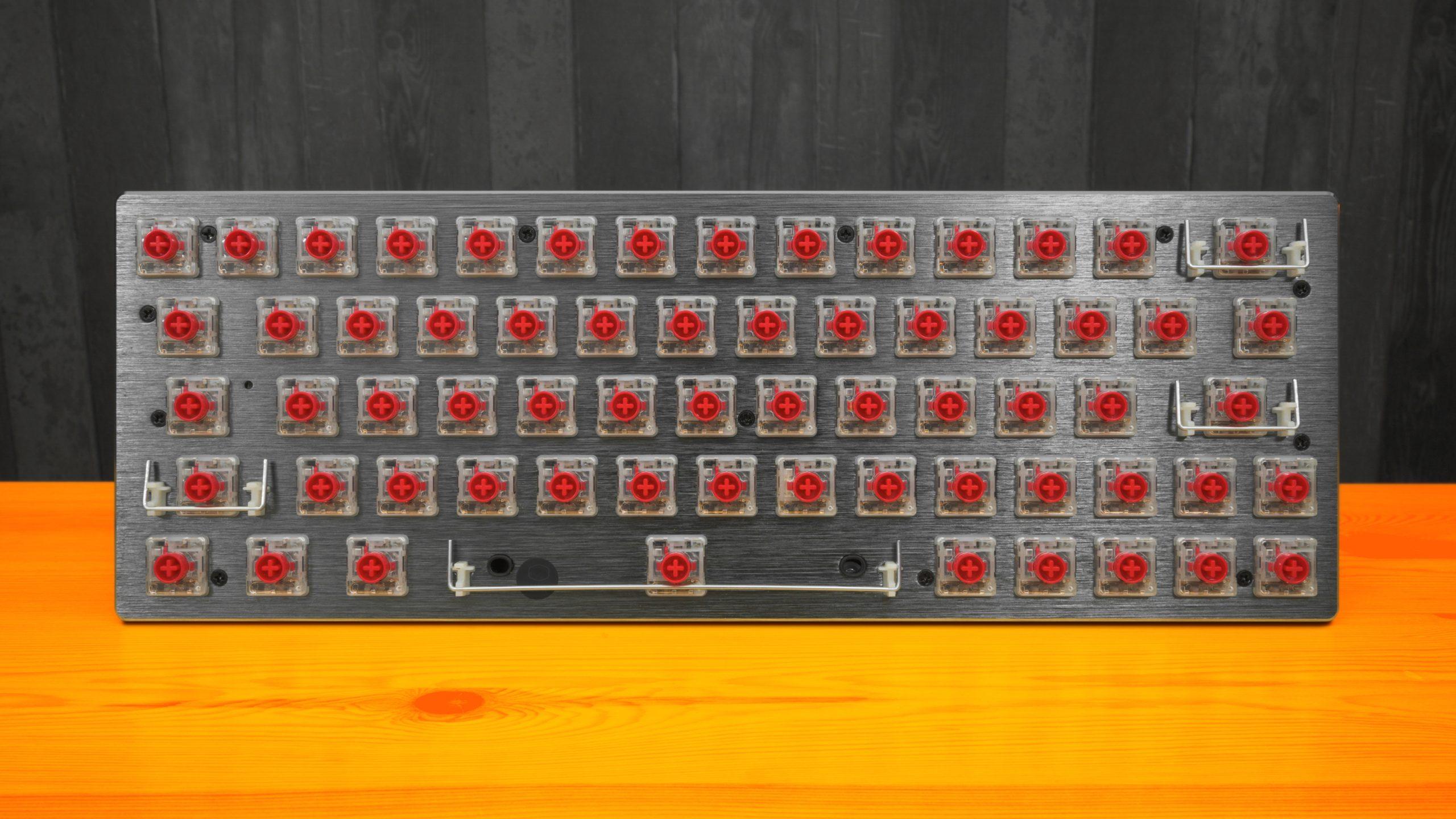 Foto van een 60% groot toetsenbord, waarvan alle keycaps geplukt zijn. Duidelijk zichtbaar zijn TTC's low-profile, lineaire KS32-schakelaars.